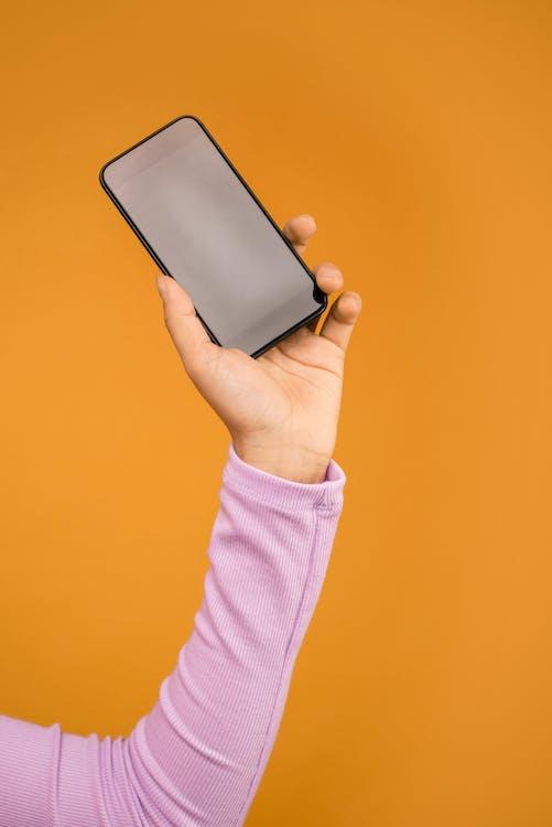 Person Holding Black Smartphone In Orange Background