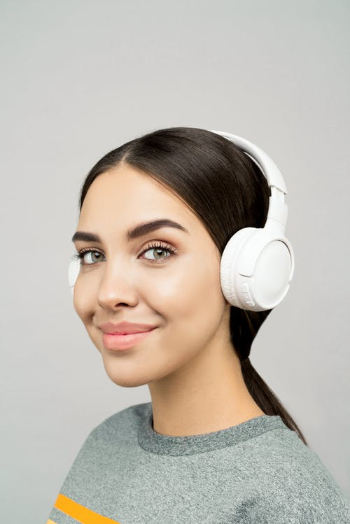 Woman Wearing Gray T-shirt and White Head Phones
