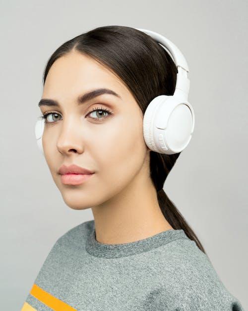Woman in Gray Crew Neck Shirt Wearing White Headphones
