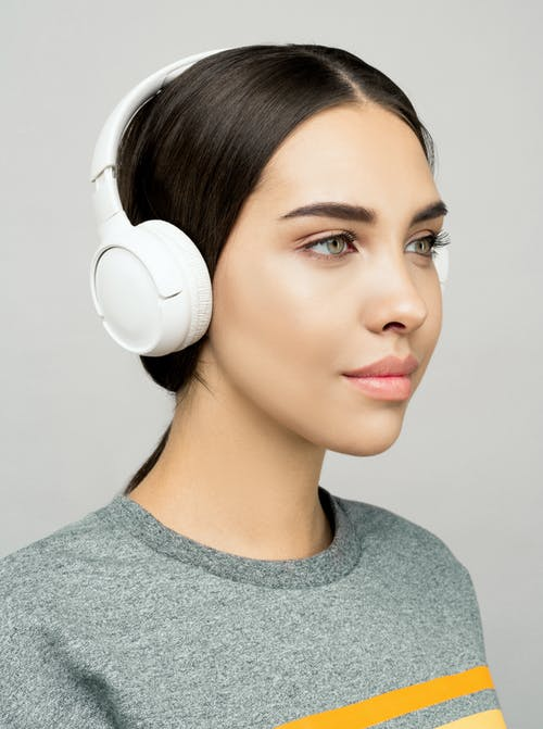 Woman in Gray Shirt Listening To Music