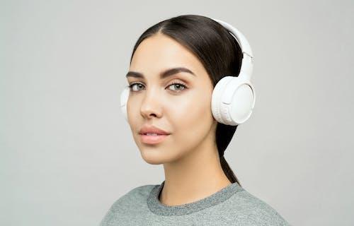 Frau Im Grauen Rundhals Hemd, Das Weiße Kopfhörer Trägt