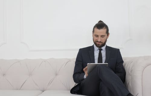 Beard Man in Black Suit Sitting on White Couch