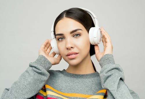 Woman in Gray and Yellow Sweater Holding White Headphones