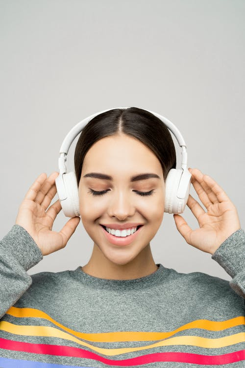 Woman in Gray Sweater Wearing White Headphones