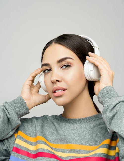 Женщина в сером свитере с наушниками