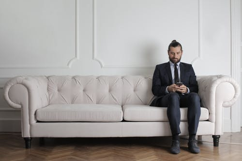 Man Sitting on White Couch Using Smartphone