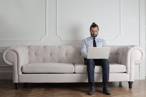 Man Wearing Blue Shirt and Tie Sitting on White Sofa Using Laptop
