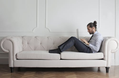 Photo Of Man Sitting On Couch