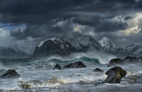 Sea Waves Crashing on Shore With Mountain in Distance Under Gray Clouds
