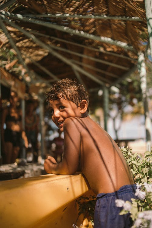 Side view cheerful ethnic shirtless boy sitting at counter with roof on sunny street