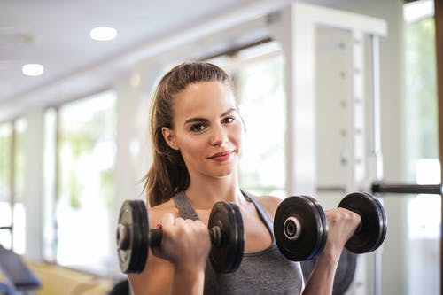 Woman in Gray Tank Top Holding Two Black Dumbbells
