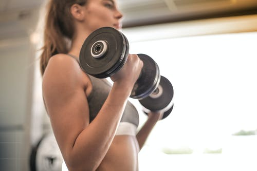 Woman in Gray Sports Bra Holding Black Dumbbell