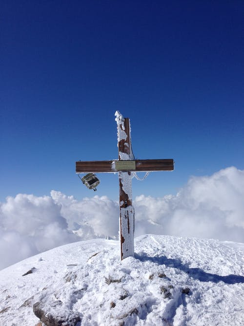 Grave cross on snowy hilltop