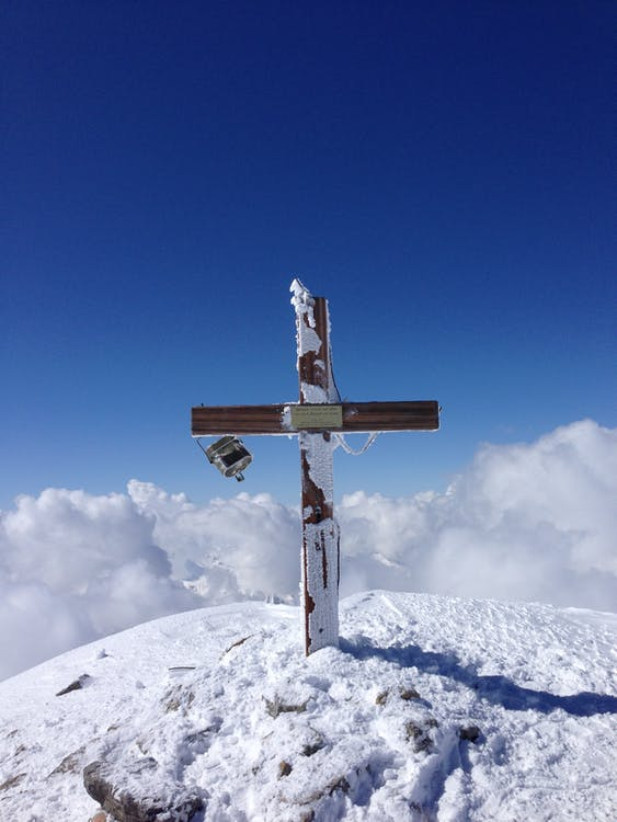 Simple wooden Christian cross with epitaph on grave covered with thick layer of snow and placed on hilltop on winter day