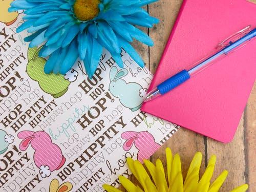 Pink Hardbound Notebook and Blue Ballpoint Pen