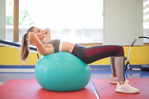 Woman in Gray Exercise Bra and Gray Leggings Lying on Blue Exercise Ball