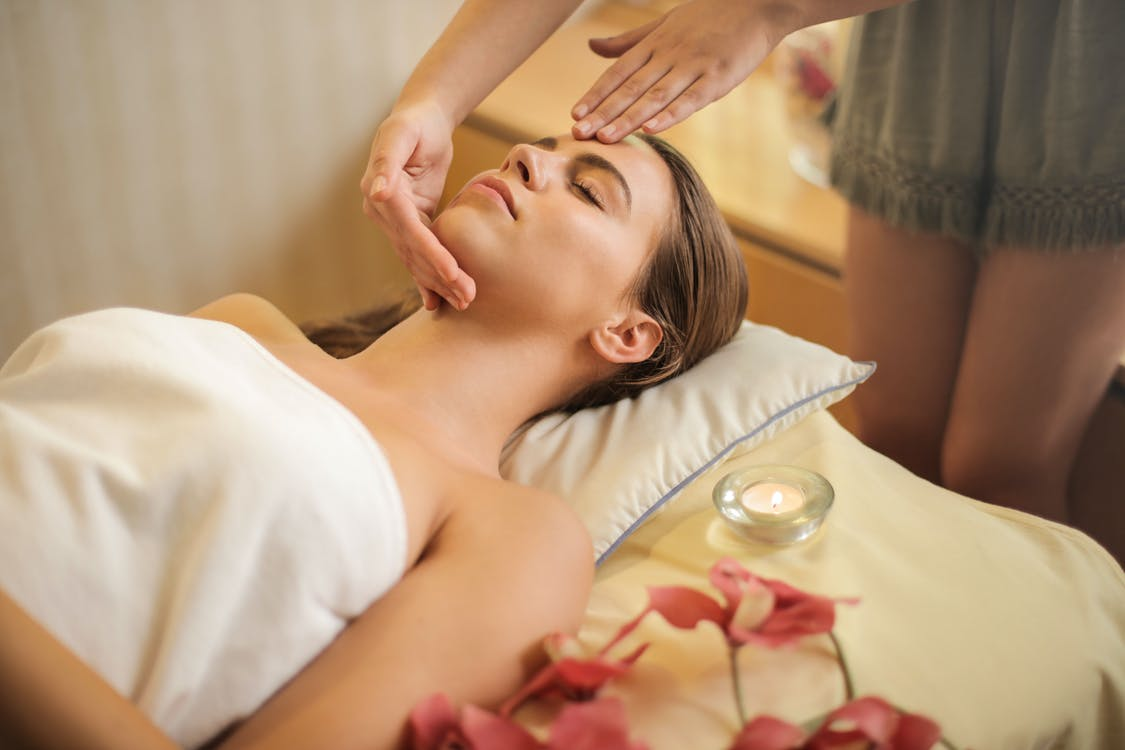 Woman in Wrapped in White Towel Lying on Bed Getting Massage