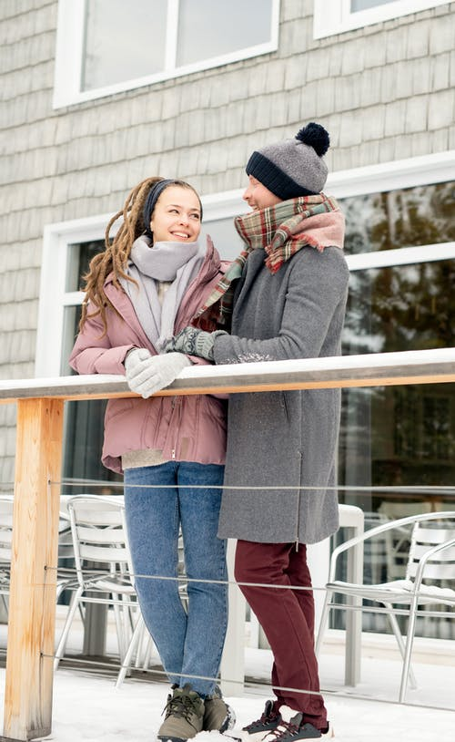 Photo Of People Leaning On Wooden Handrail