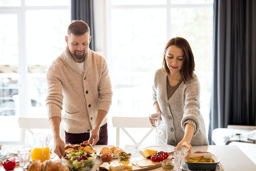 Man And Woman Preparing The Table