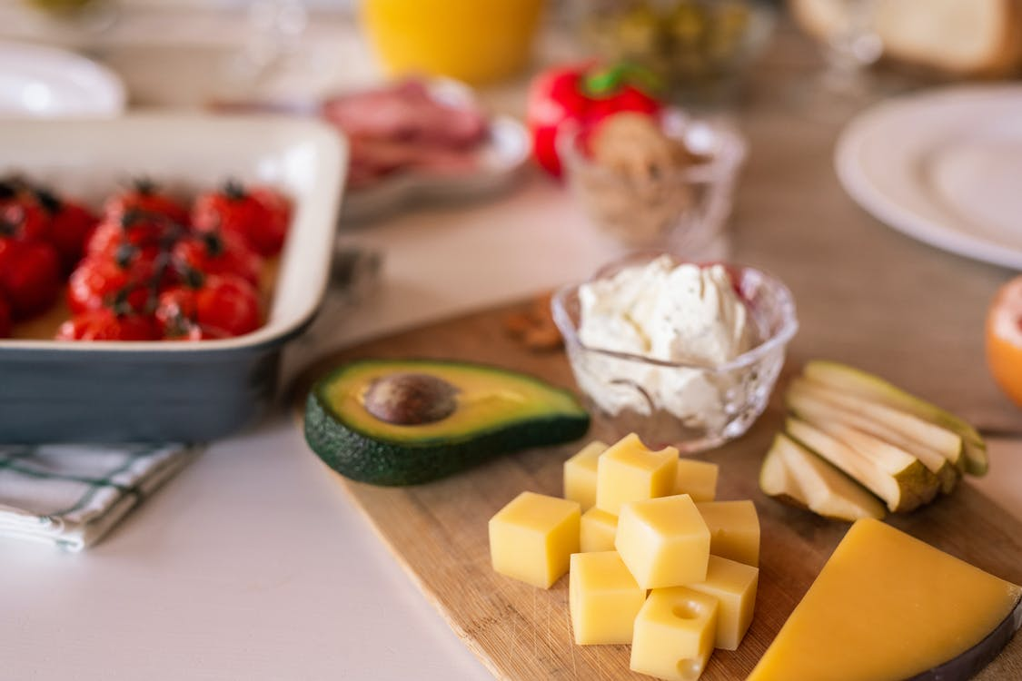 茶色の木製まな板にスライスしたチーズ