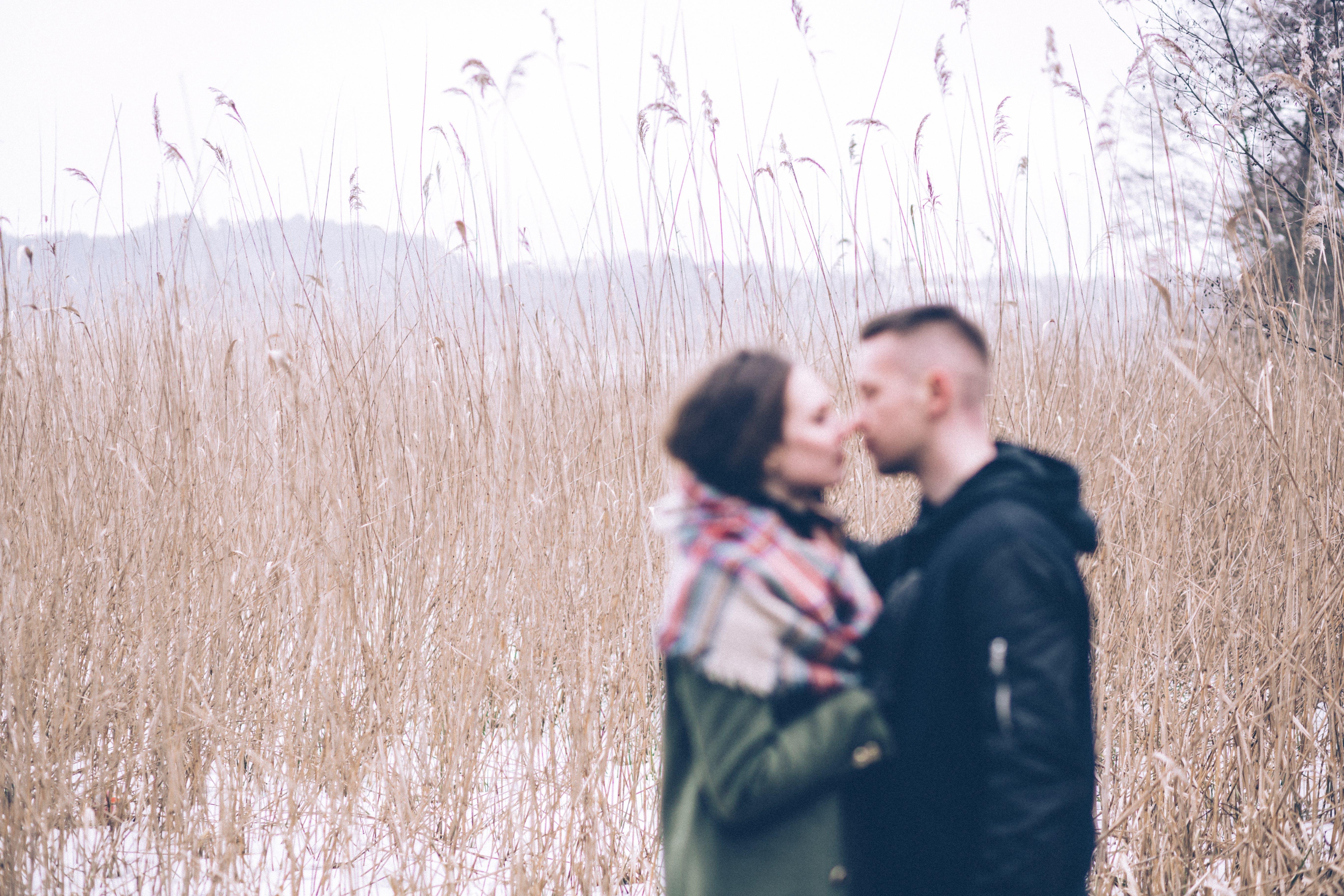 Man and Woman Standing Near Grass Field