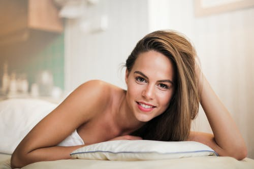 Topless Woman Lying on Bed Wrapped in White Towel