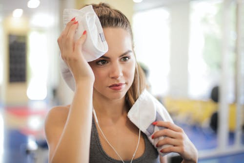 Selective Focus Close-up  Photo of Woman in Gray Tank Top Using White Towel to Wipe Her Face