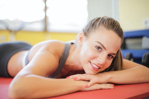 Close-up Photo of Smiling Woman in Gray Tank Top Laying Down on Red Yoga Mat