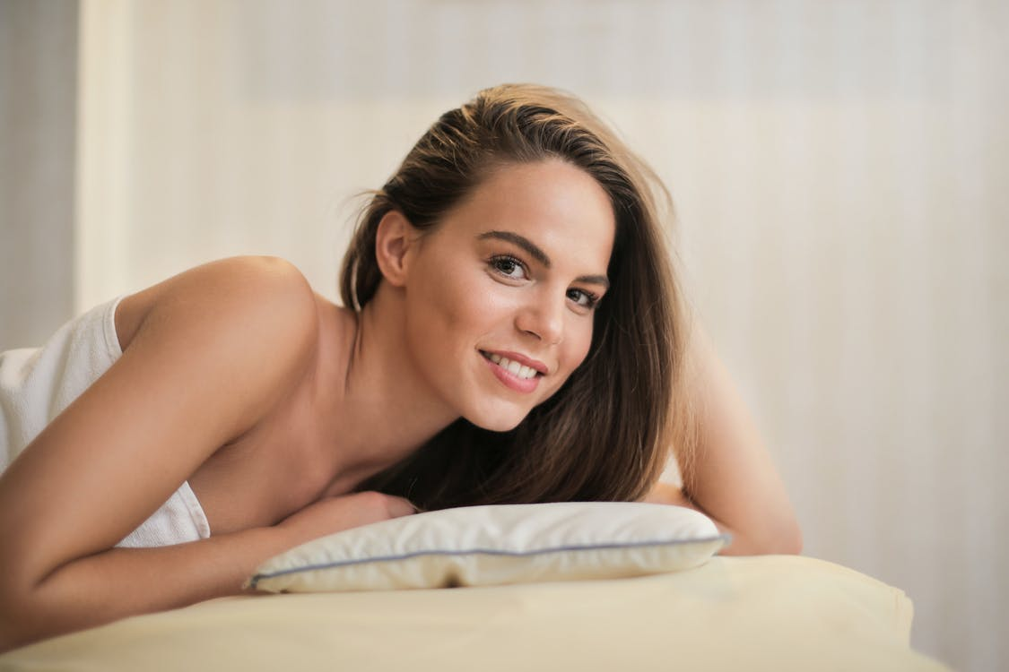 Selective Focus Photo of Smiling Woman in White Towel Lying on Massage Bed