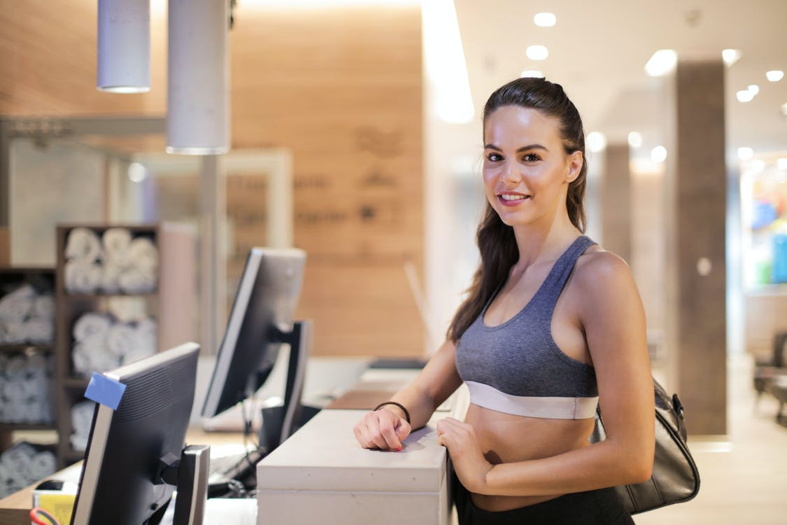 Glad sportswoman in trendy bra standing near counter in gym and waiting for receptionist while smiling and looking at camera