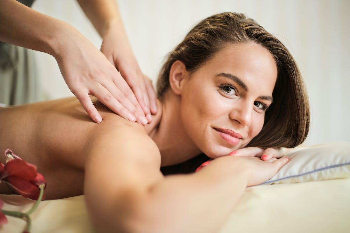 Frau, Die Auf Weißem Bett Liegt, Das Massage Erhält