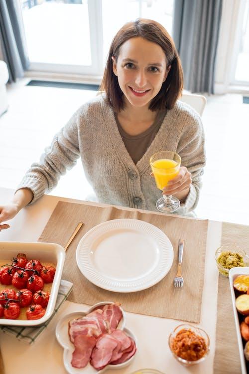 Woman In Gray Cardigan Holding An Orange Juice