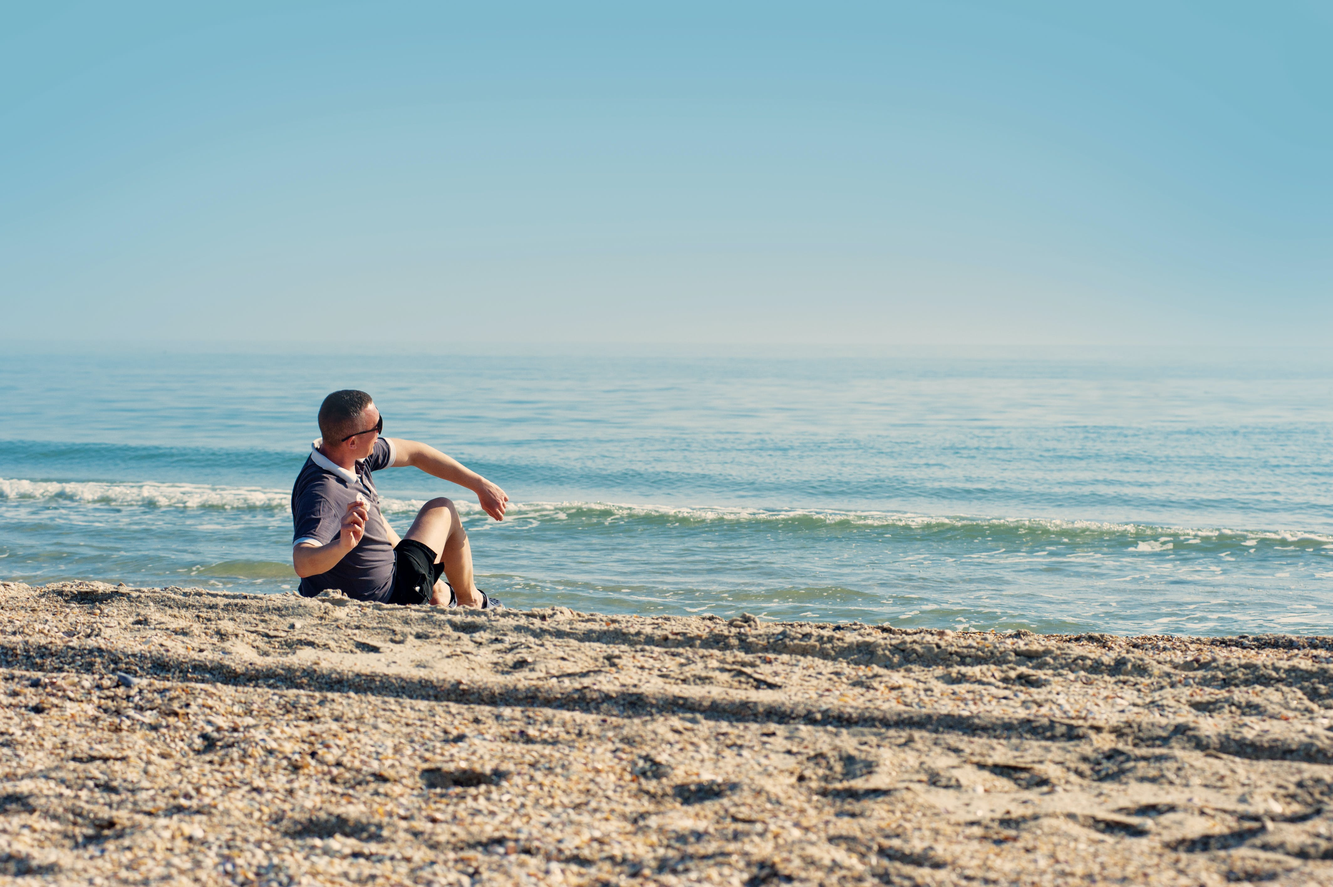 Man Sitting on Seashore