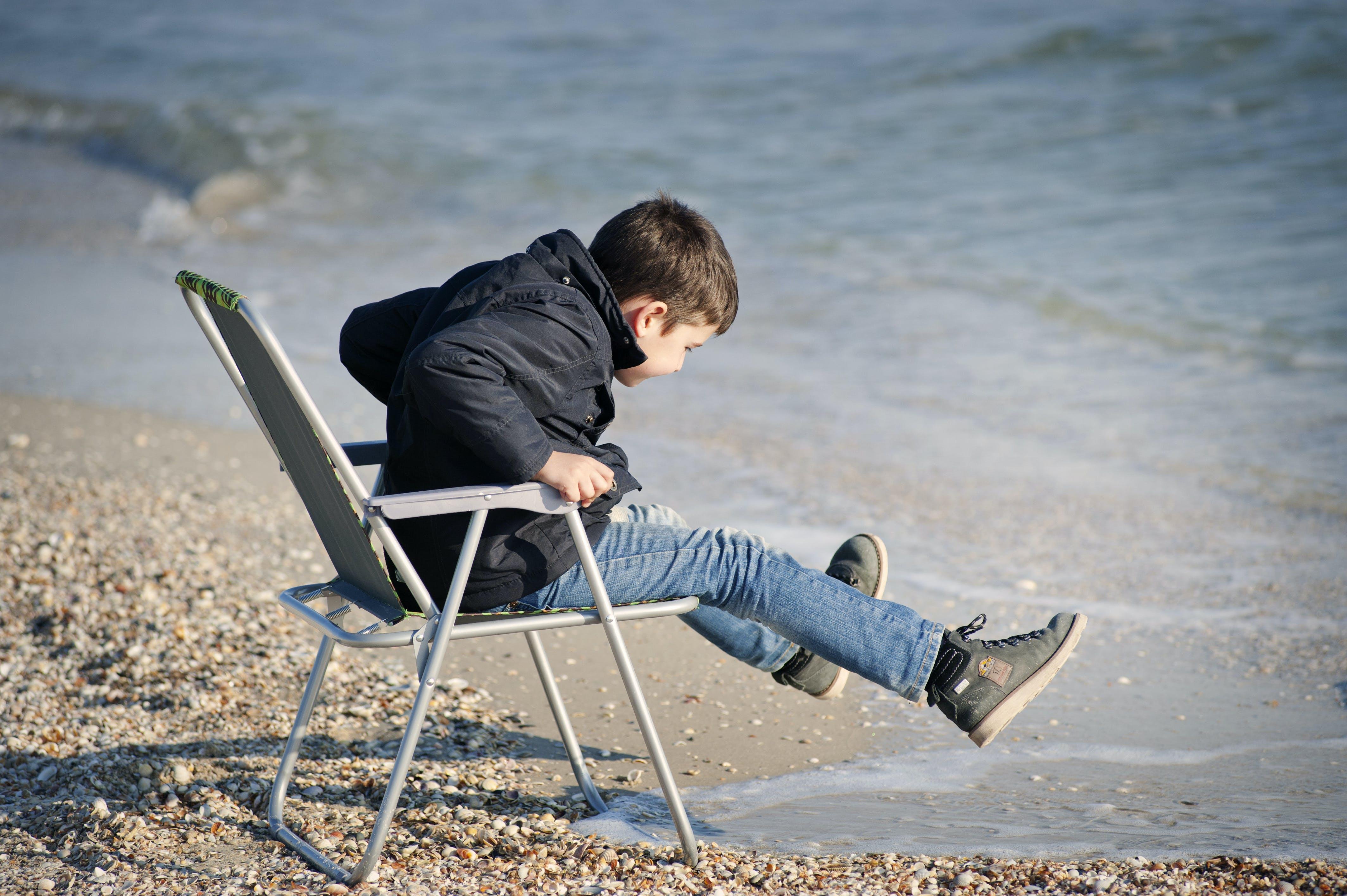 Boy Sitting on Chair Beside Seashore