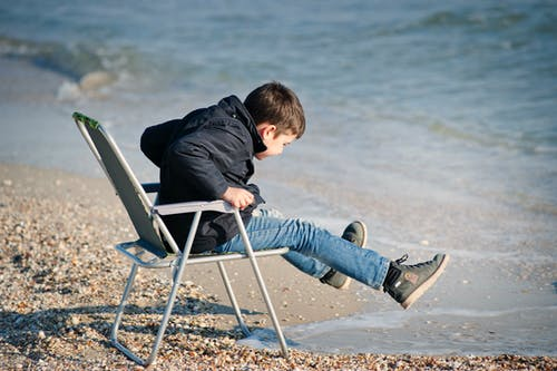 Boy Sitting on Chair Beside Seashore