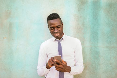 Man in White Dress Shirt Holding Black Smartphone Smiling