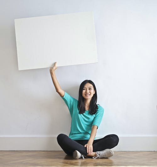 Cheerful Asian woman sitting cross legged on floor against white wall in empty apartment and showing white blank banner