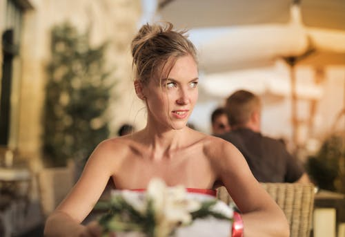 Selective Focus Photo of Woman in Red Tube Top  Sitting Alone at a Table Looking Away