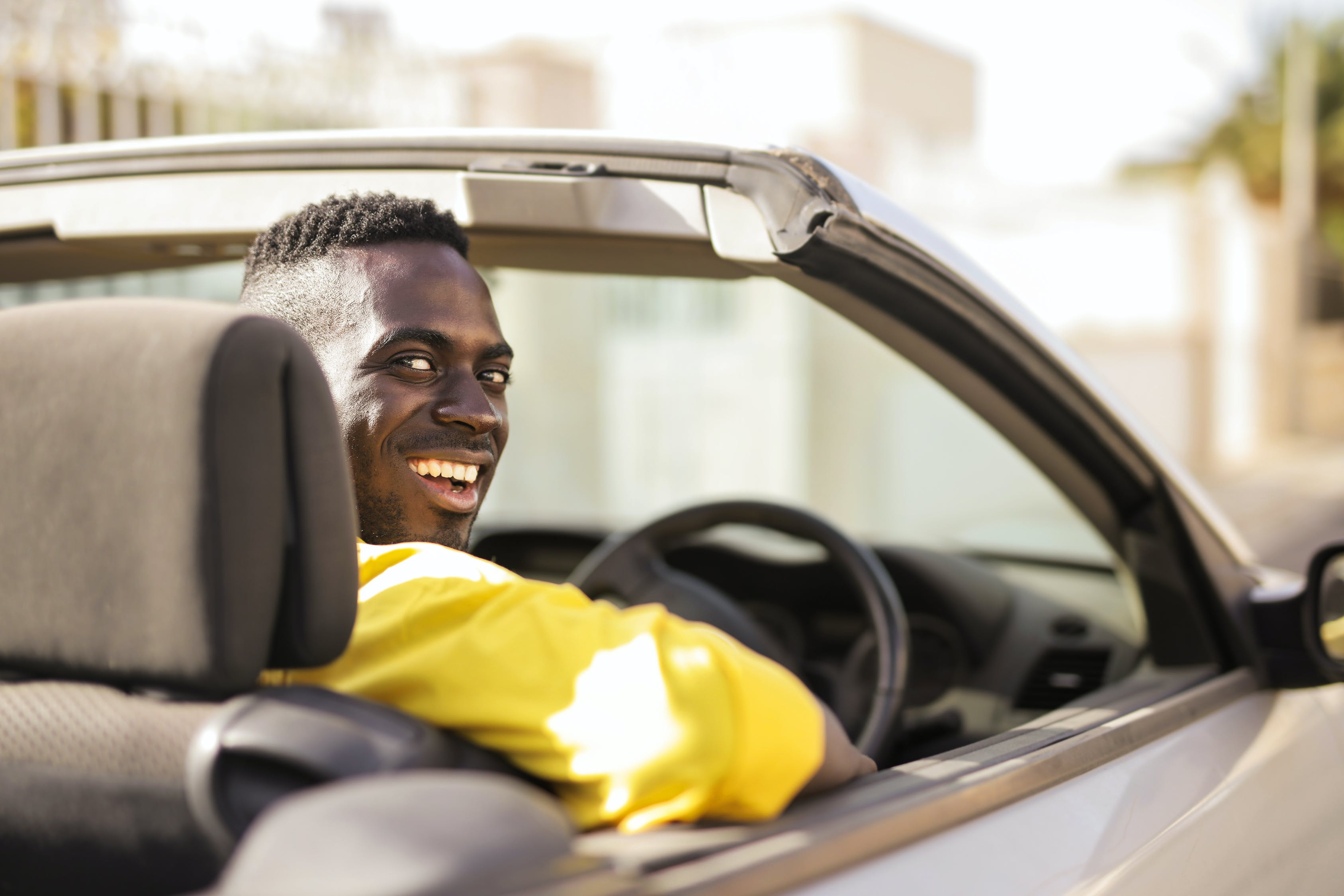 Man in Yellow Shirt Driving A White Luxury Car