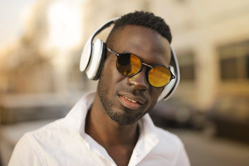 Selective Focus Close-up Photo of Man in White Shirt Wearing Black Sunglasses and White Headphones