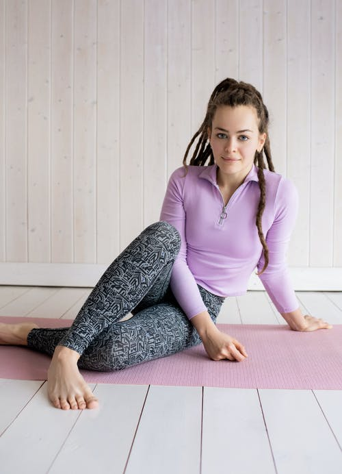 Woman in Purple Long Sleeve Shirt and Gray Pants Sitting on Purple Yoga Mat