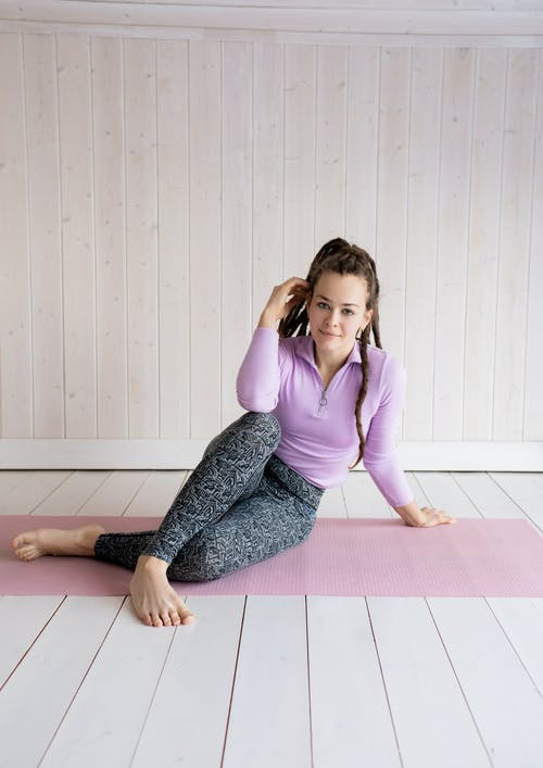 Woman in Purple Long Sleeve Shirt and Gray Pants Sitting on Floor