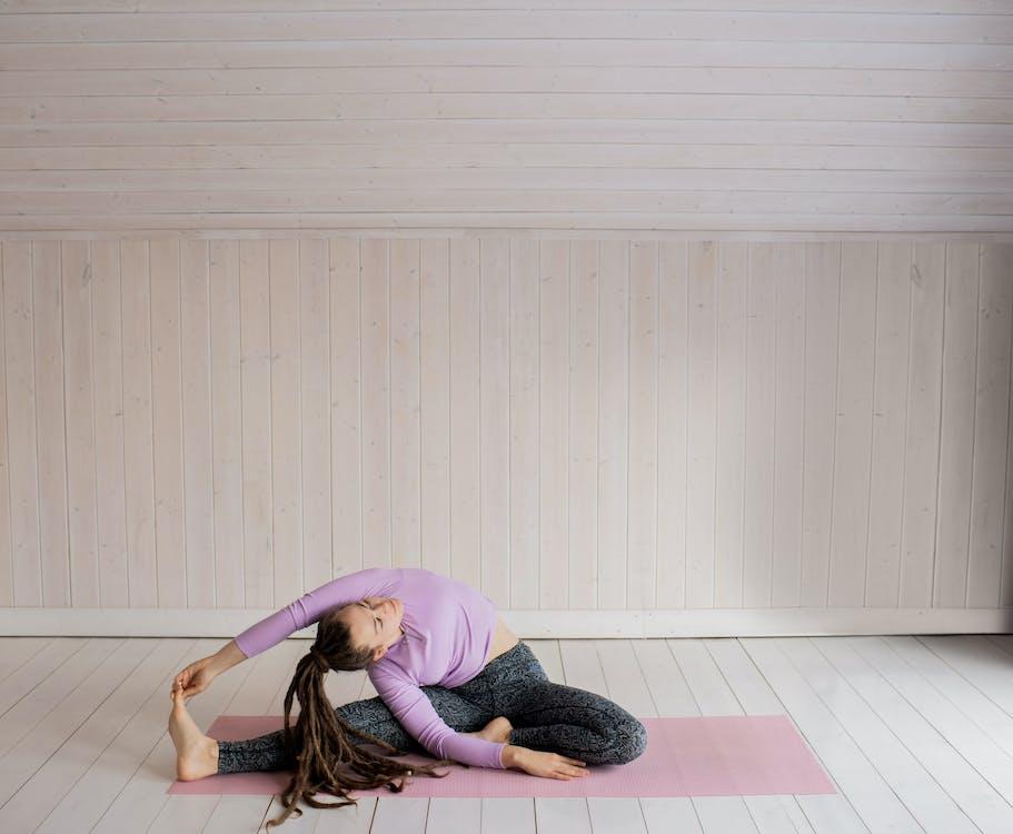 Woman in Purple Long Sleeve Shirt and Black Pants Lying on Floor