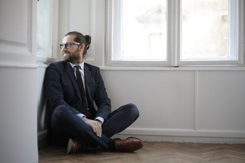 Photo of Smiling Man in Black Suit Sitting on Brown Wooden Floor by the Corner Looking Outside a Window