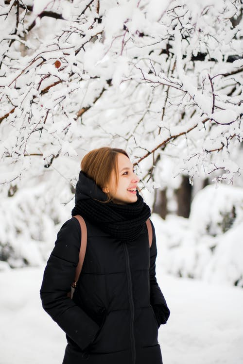 Photo of Smiling Woman in Black Winter Coat Standing Near Snow Covered Tree