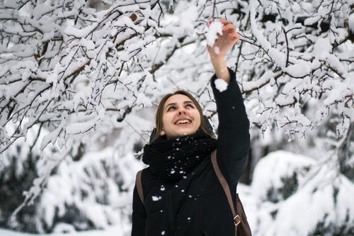 Photo of Smiling Woman in Black Winter Coat Standing Under Snow Covered Tree