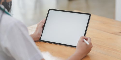 Photo Of Person Holding Tablet