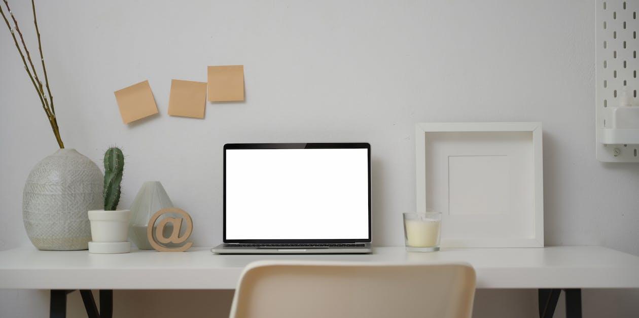 Black Frame Laptop  on White Table Near Glass of Milk