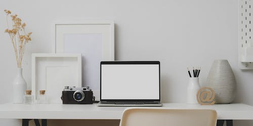 Black Frame Laptop and Camera On White Table