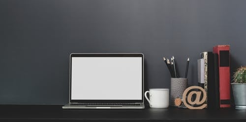 Laptop Beside White Ceramic Mug on Black Table